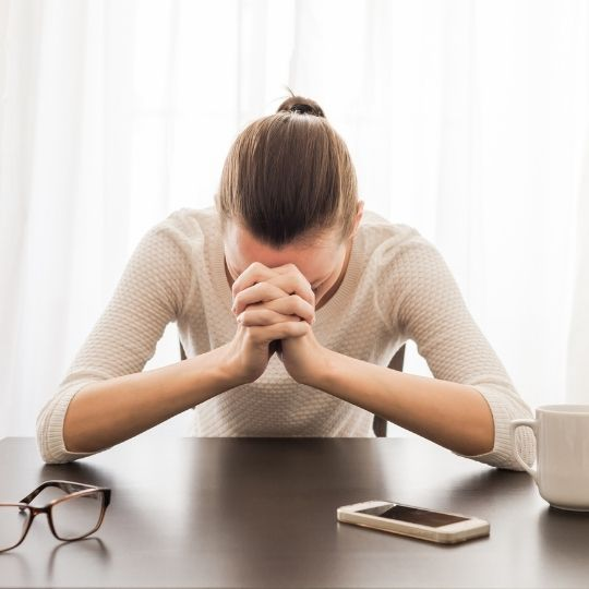 Stressed woman with head on hands.